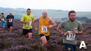 Two runners from the Steel City Striders running across the moorland.